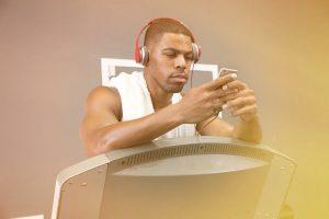 man looking at iphone before treadmill running