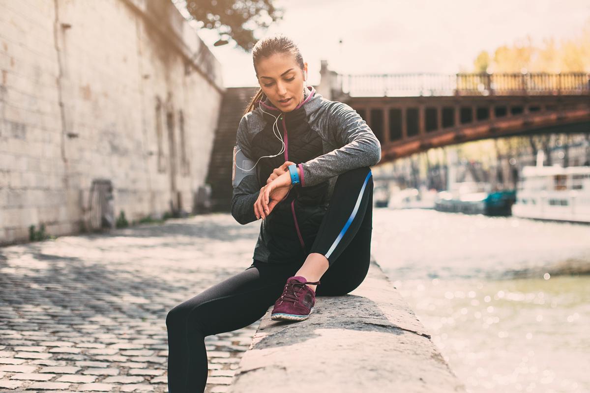 woman runner checking her smart watch