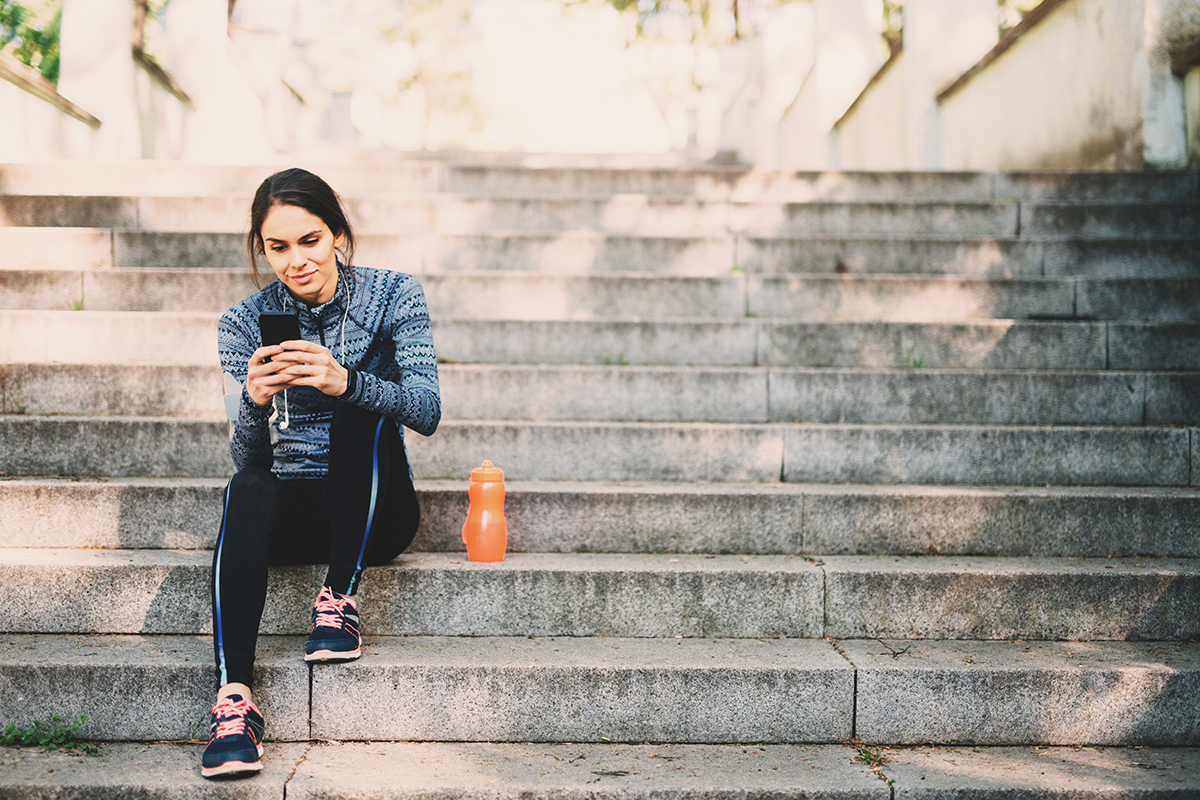 woman sitting down after workout outdoors