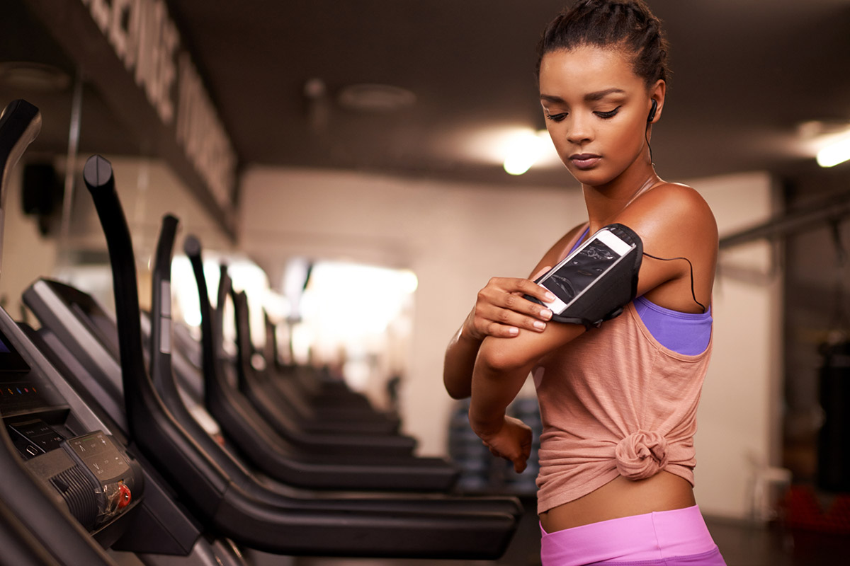 woman checking her iphone on treadmill