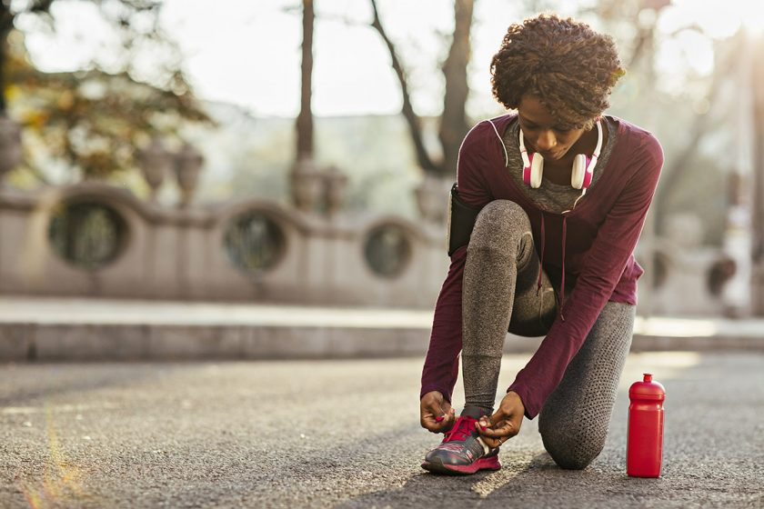 woman tying her shoe outdoors