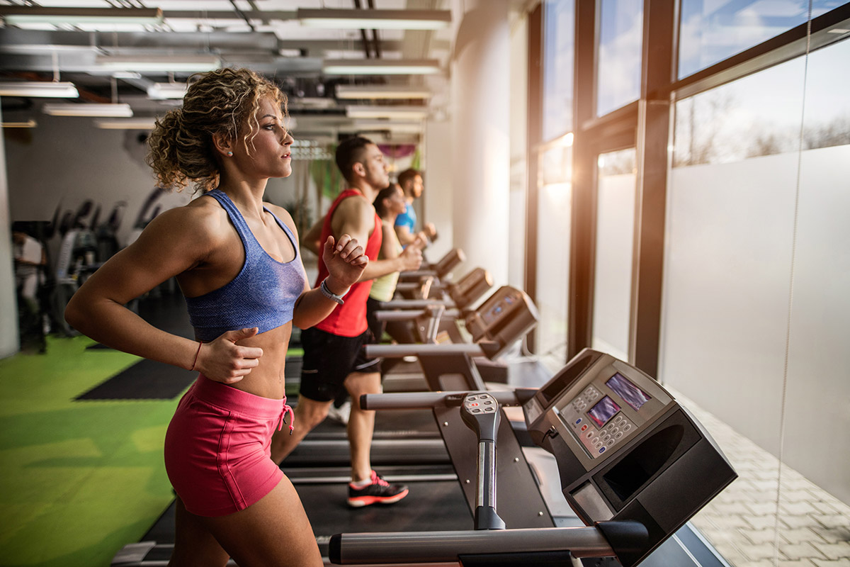 woman with curly hair running on treadmill with headphones