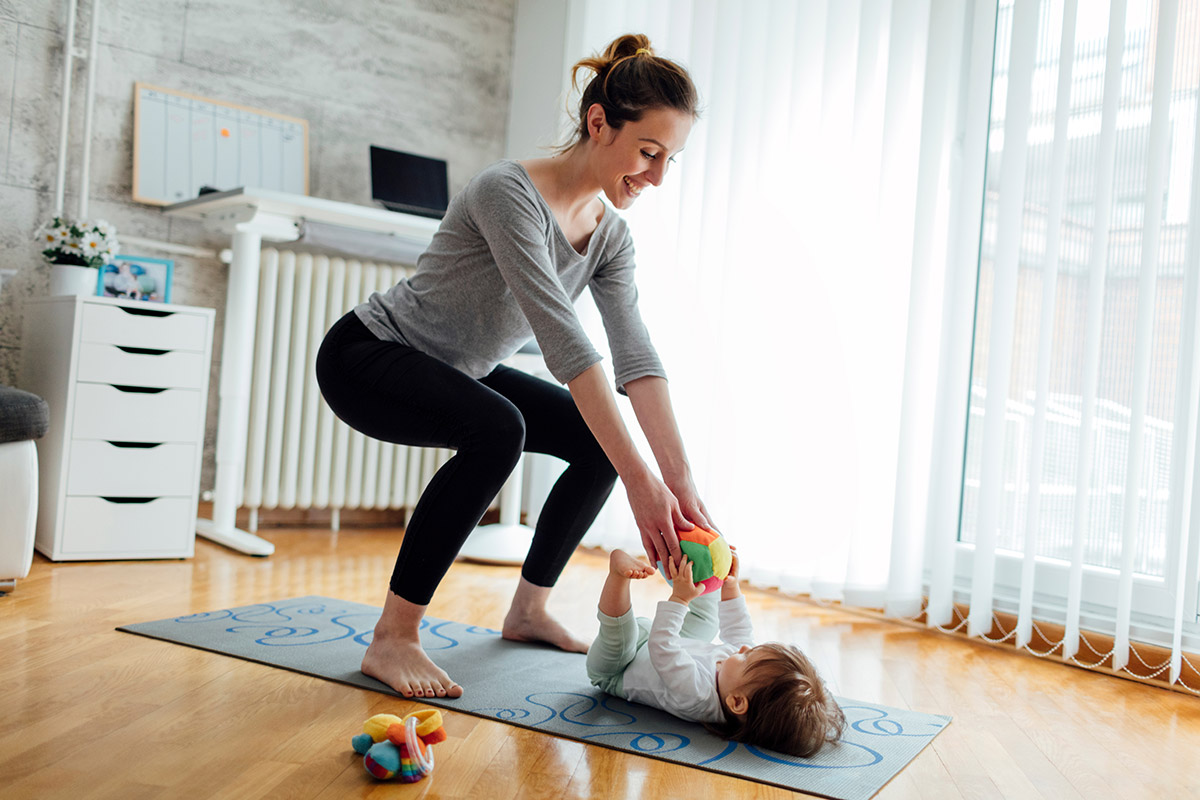 breastfeeding mom working out with baby