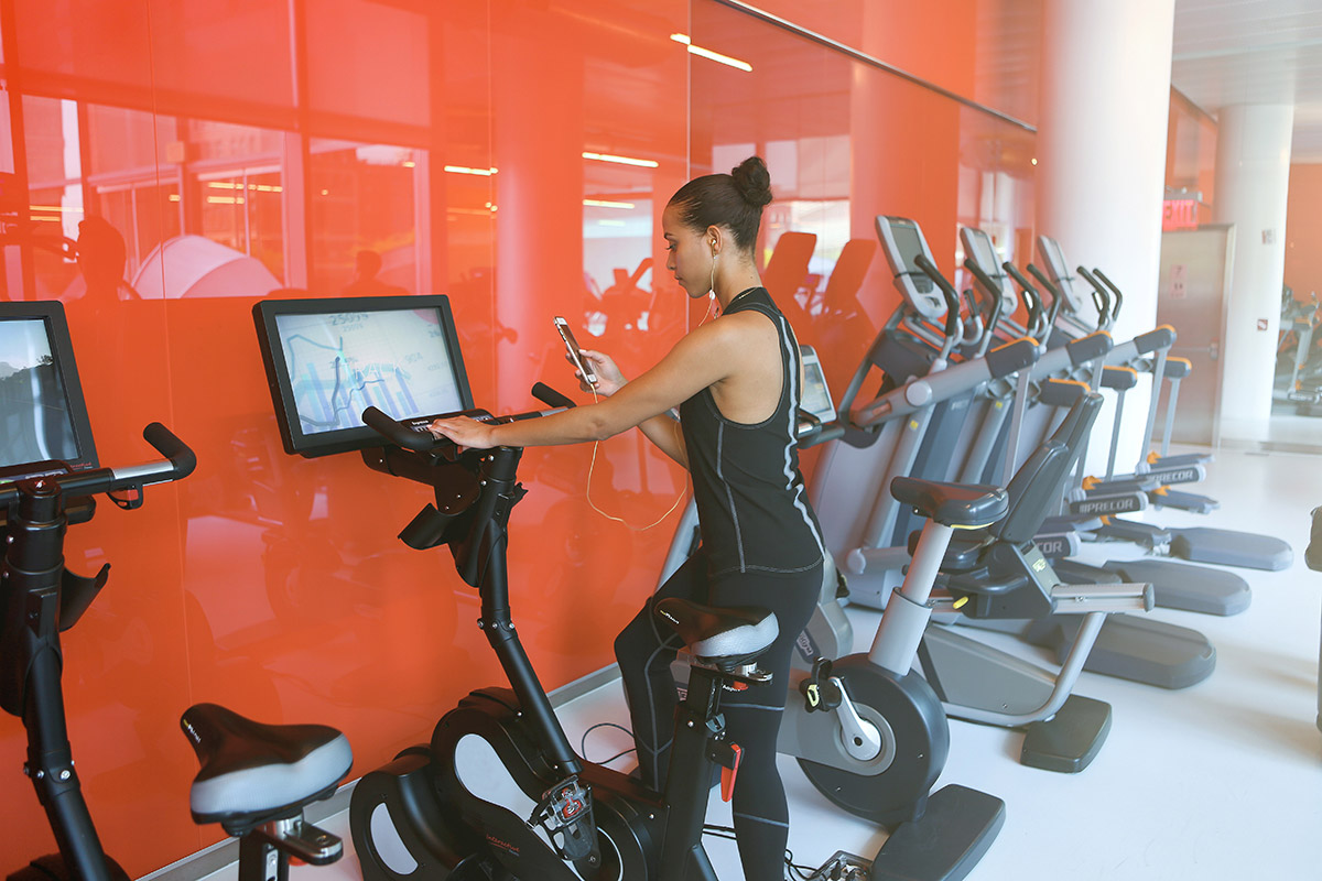 woman getting on stationary bike at the gym worried about germs