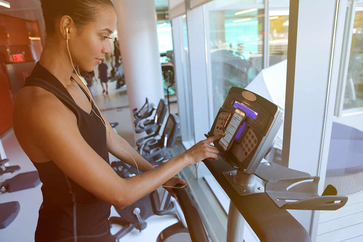 beginner woman pressing buttons on stair climber cardio machines at the gym