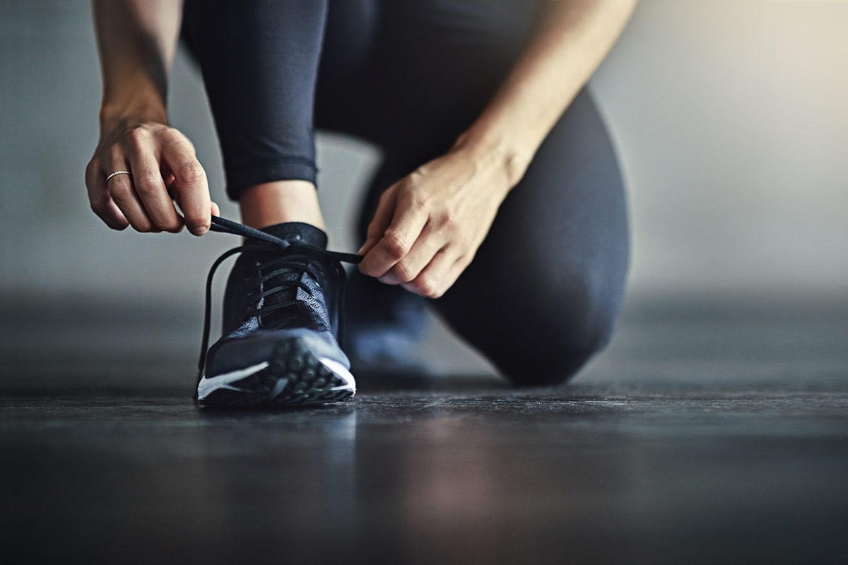 woman ties shoe for workout routine