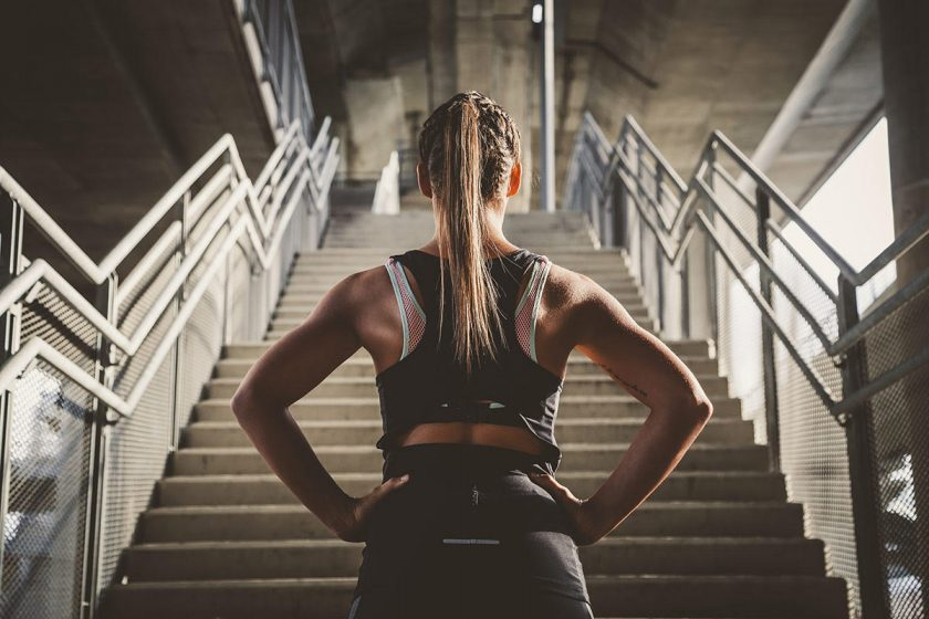 fitness woman by stairs, aaptiv trainer diary