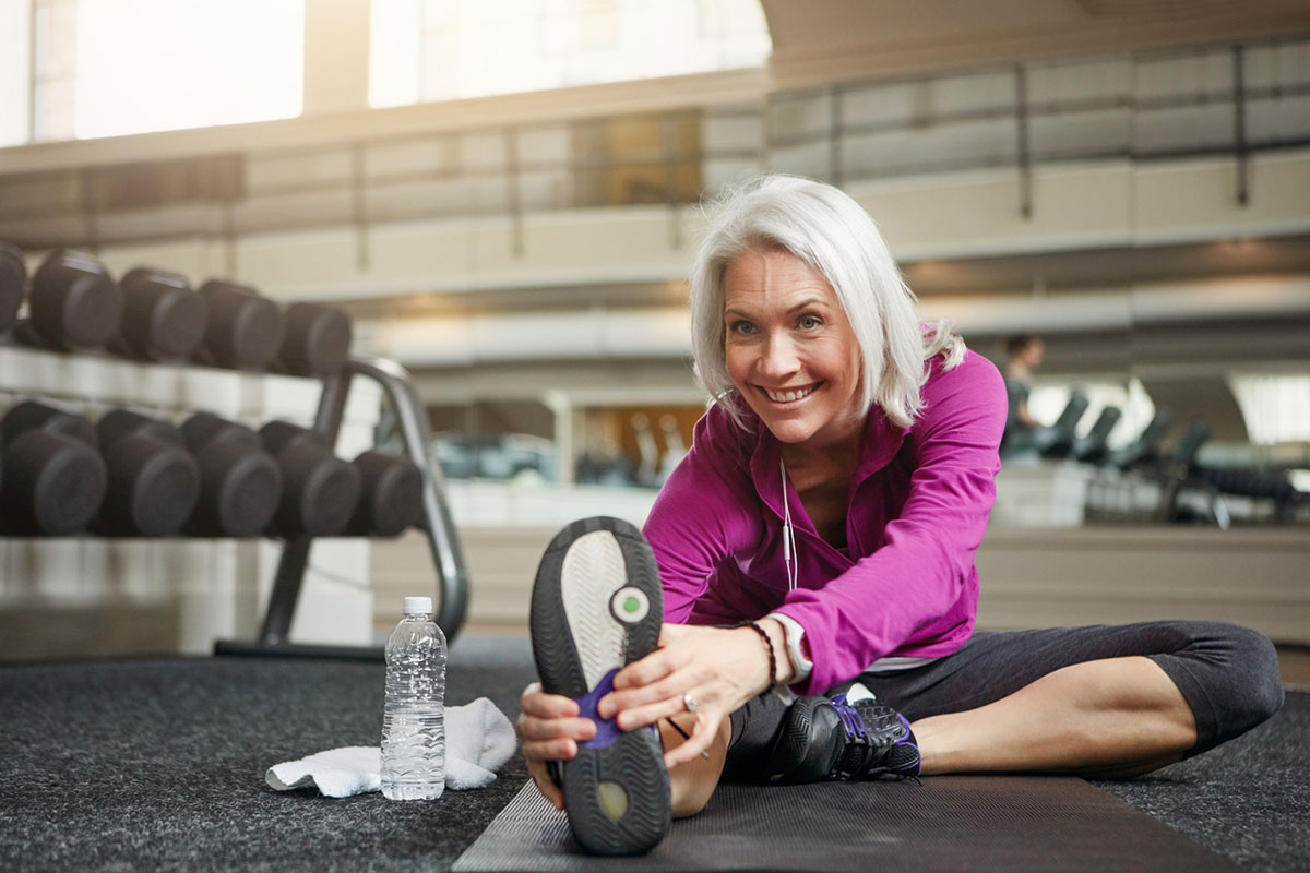 woman stretches in gym before scale