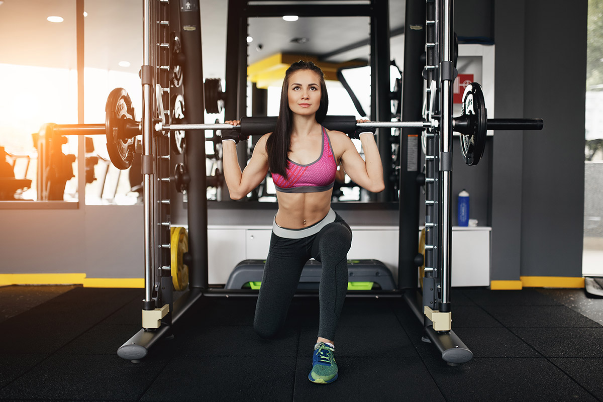 woman squats in smith machine