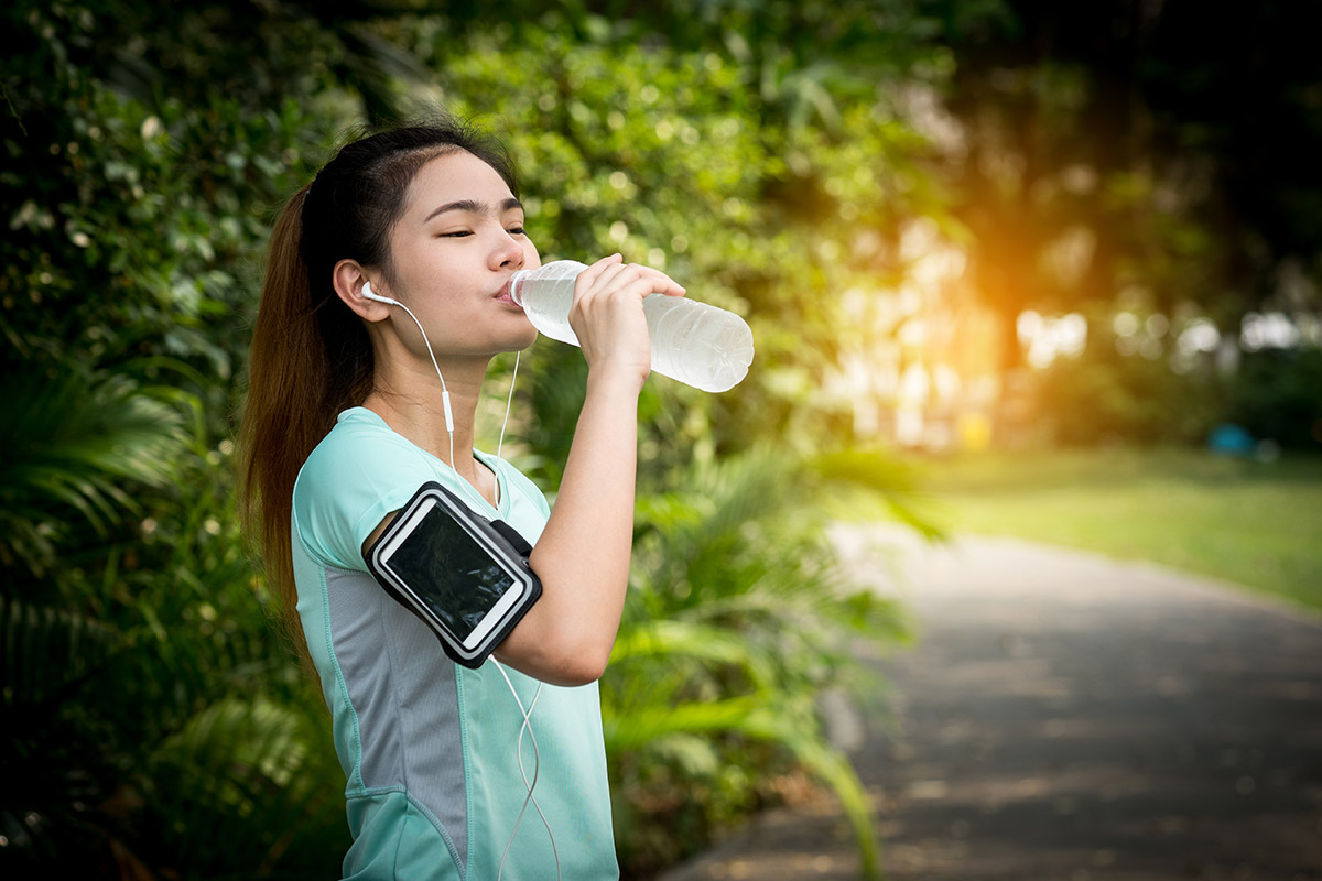runner drinks water to stay hydrated on a long run