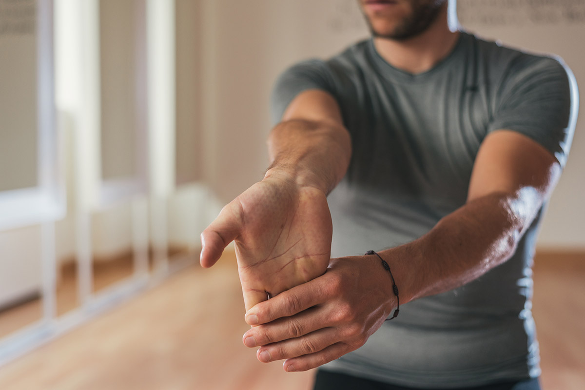 man does wrist and arm stretches